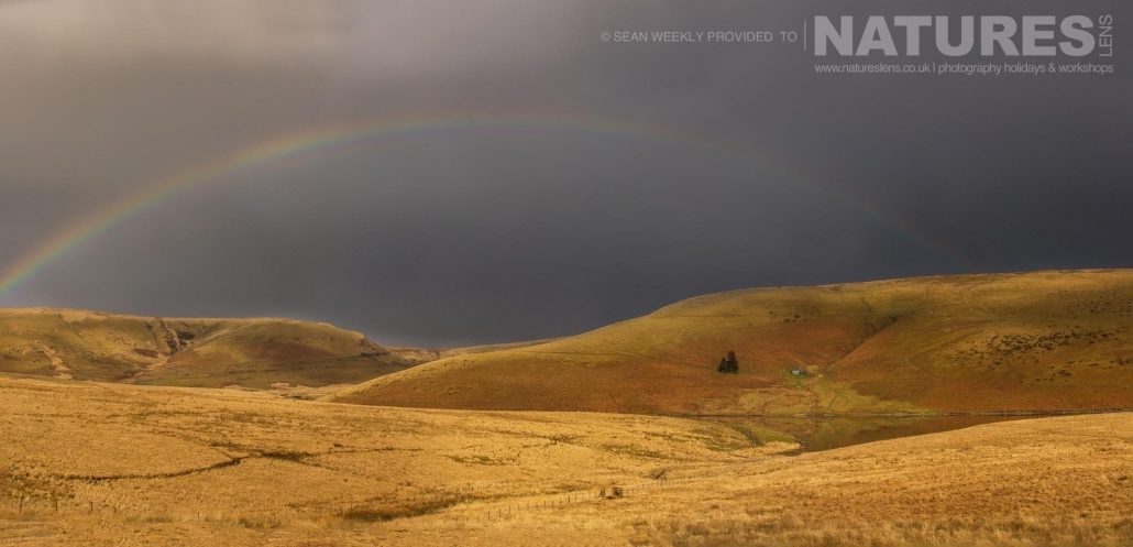 A rainbow appears over the mountainous landscape of the Elan Valley - typical of the type of image captured on the NaturesLens Mid-Wales Landscapes Photography Workshop